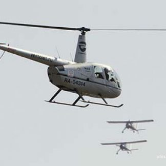 Helicopter flying with planes R44 © alexander Markin 2014